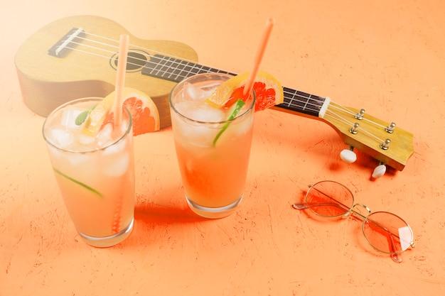 アイスキューブと柑橘系のジュースのグラス。サングラスとウクレレのオレンジ色のテクスチャ背景 無料写真
