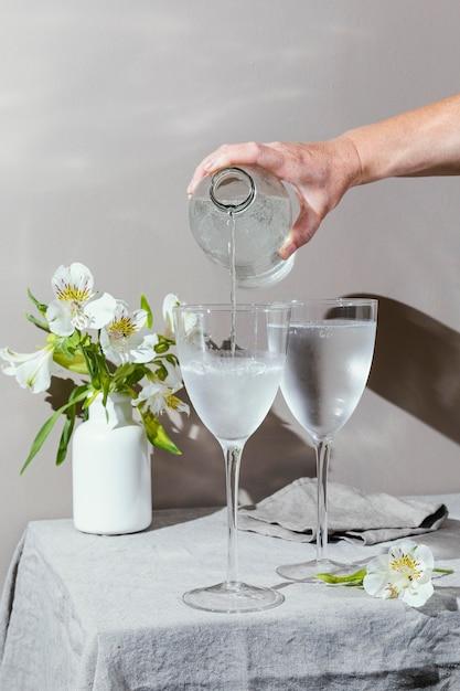 テーブルの上の水と花のグラス 無料写真