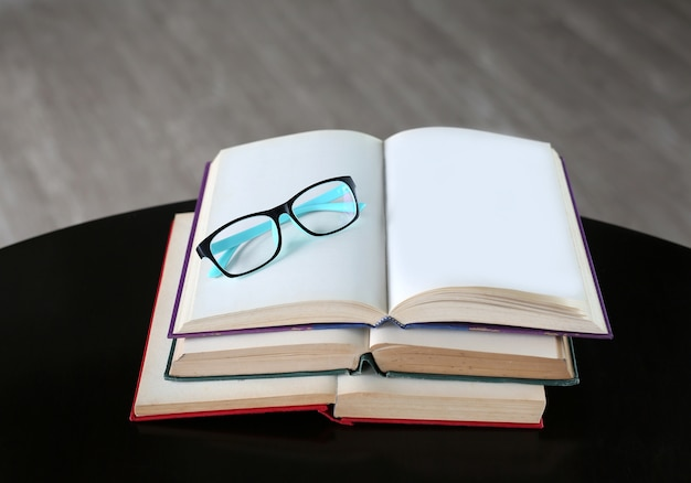 Glasses on open book on wooden table. Premium Photo