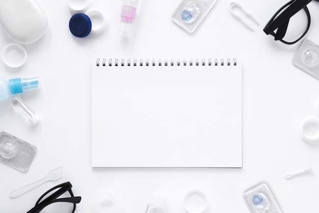Glasses and optical objects with notebook mock-up on white background Free Photo
