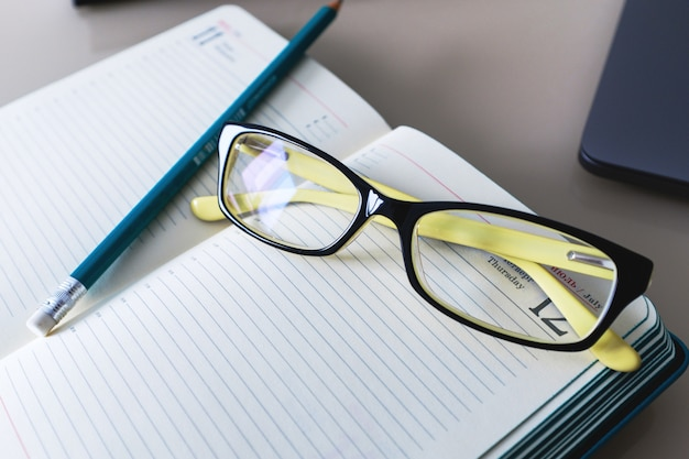Glasses and a pencil are on the notebook. education. business. Premium Photo