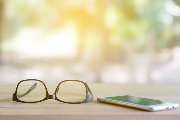 Glasses on the phone are placed on the table. Premium Photo