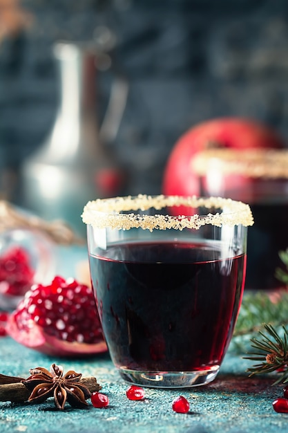 A glasses of pomegranate juice with fresh pomegranate fruits and fir tree branches on blue table Premium Photo
