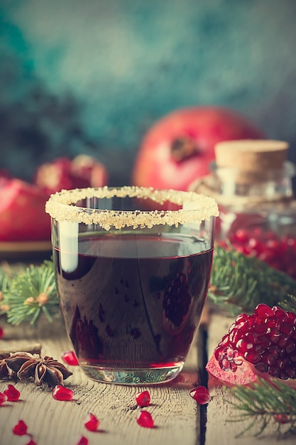 A glasses of pomegranate juice with fresh pomegranate fruits and fir tree branches on wooden table Premium Photo