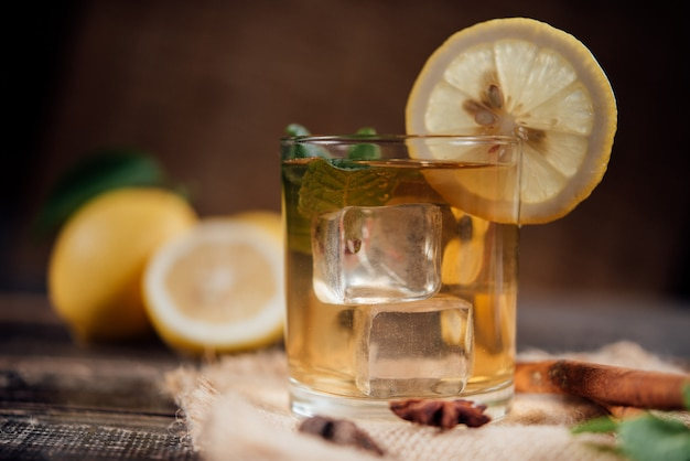 Glasses of  tea with lemon,sliced lemons on a chopping board Free Photo