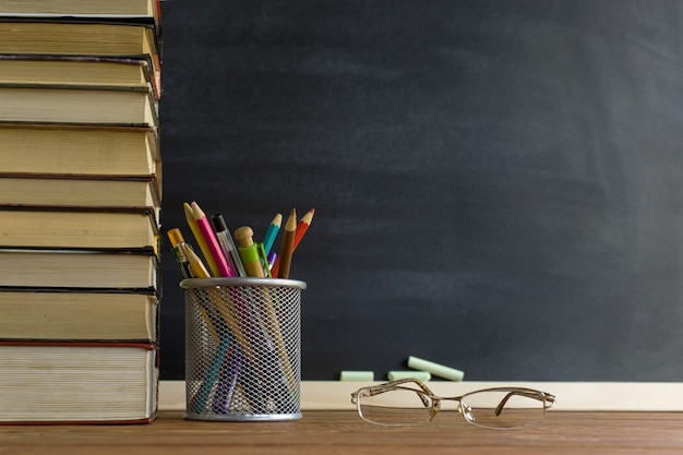Glasses teacher books and a stand with pencils on the table, on the background of a blackboard with chalk Premium Photo