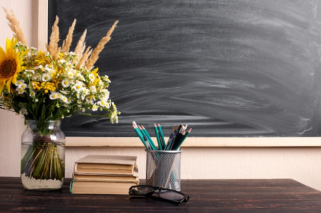 Glasses teacher books and wildflowers bouquet on the table, blackboard with chalk. the concept of the teacher's day. copy space. Premium Photo
