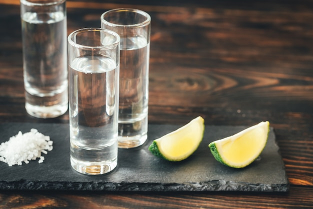 Glasses of tequila with lime wedges Premium Photo