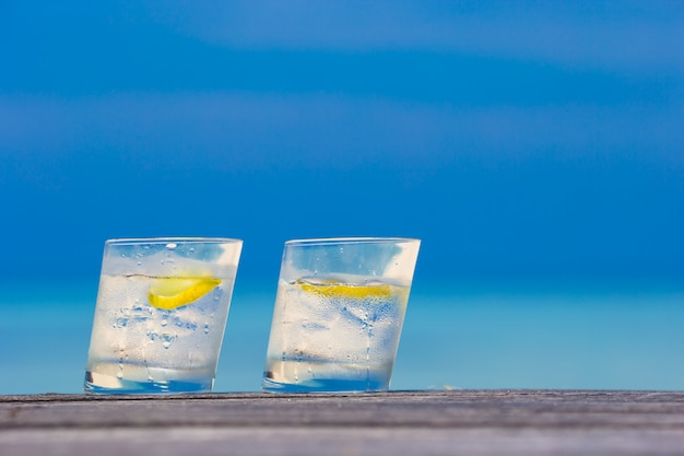 Glasses of waters with lemon on wooden on sea background Premium Photo