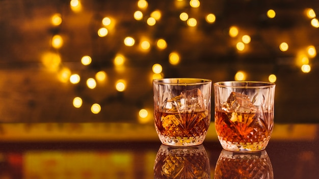 Glasses of whiskey with bokeh effect Free Photo