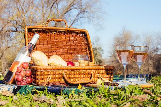 Glasses of wine next to picnic basket Free Photo