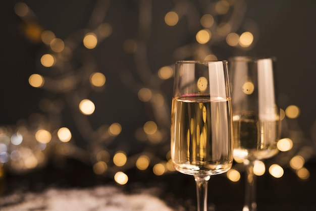 Glasses with drink near fairy lights Free Photo