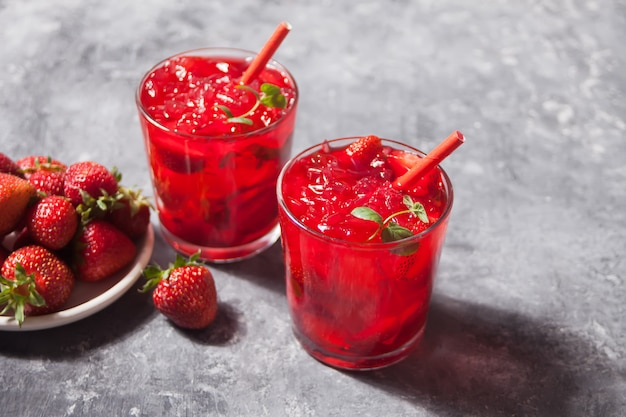 Glasses with fresh homemade strawberry sweet iced tea or cocktail, lemonade with mint. refreshing cold drink. summer party. Premium Photo