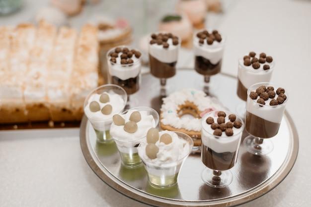 Бокалы с порцией кремовых десертов стоят на столике Бесплатные Фотографии
