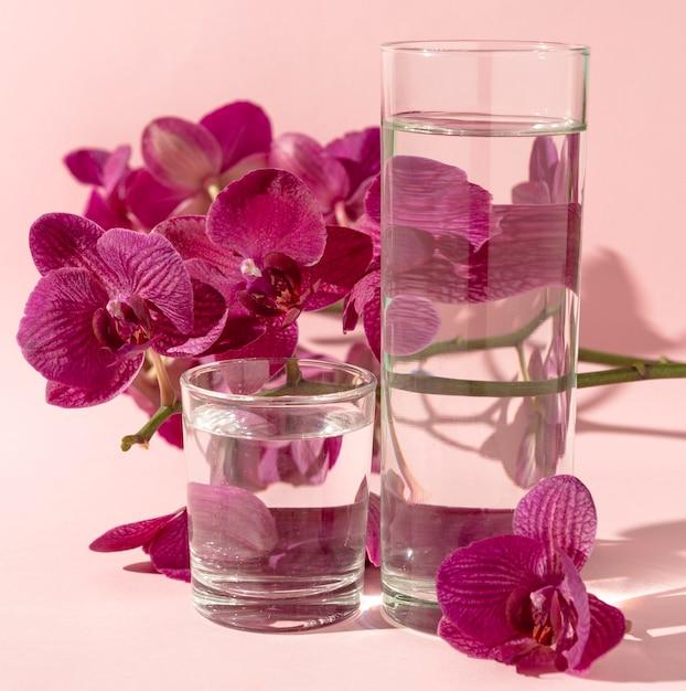 Bicchieri con acqua accanto ai fiori Foto Gratuite