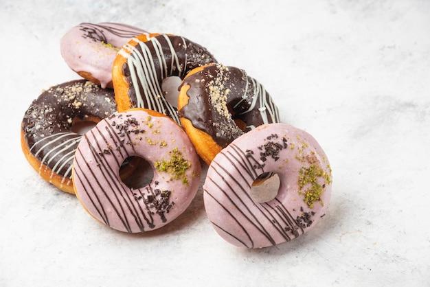 대리석 표면에 유약을 바른 초콜릿과 핑크 도넛. 무료 사진