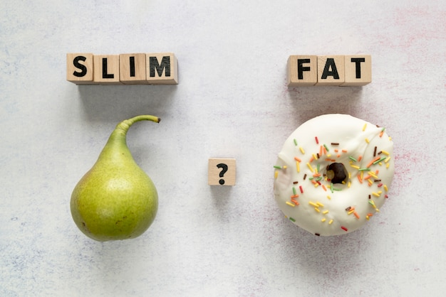 Glazed donut; pear and slim; fat text with question mark on wooden block over concrete surface Free Photo
