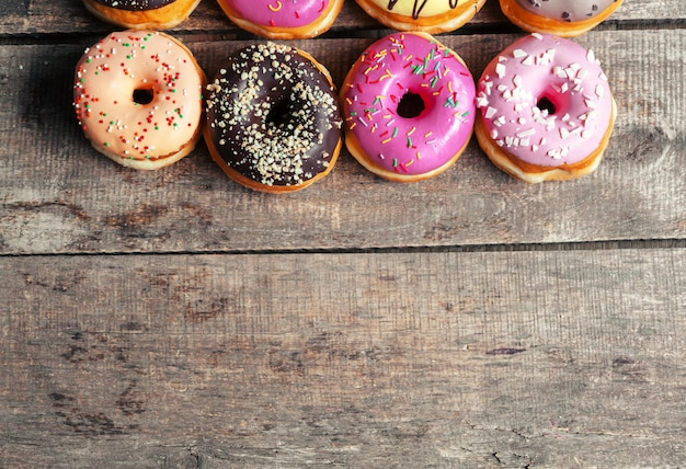 Glazed donuts on wooden background Premium Photo