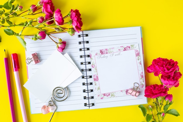 ピンクの文房具と花で黄色の背景にメモとto doリストのグライダー。ビジネスコンセプトです。上面図 無料写真