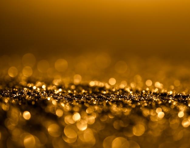 Glitter sparkle vintage lights background. dark gold and black. defocused . Premium Photo