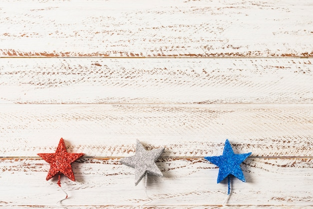 free photo glittering silver red and blue stars on white wooden textured background glittering silver red and blue stars