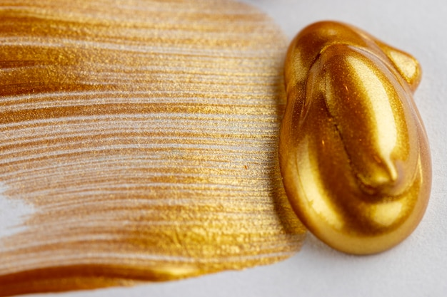 Glittery golden paint on white background Free Photo