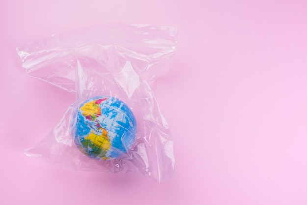 Globe in polyethylene bag over pink backdrop Free Photo