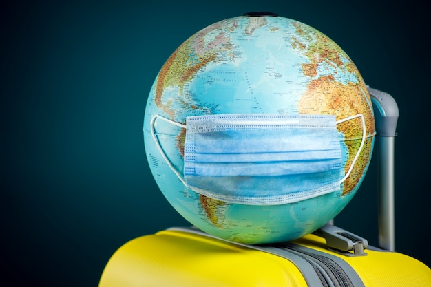 Globe with medical face mask on luggage. travel and coronavirus concept. Premium Photo