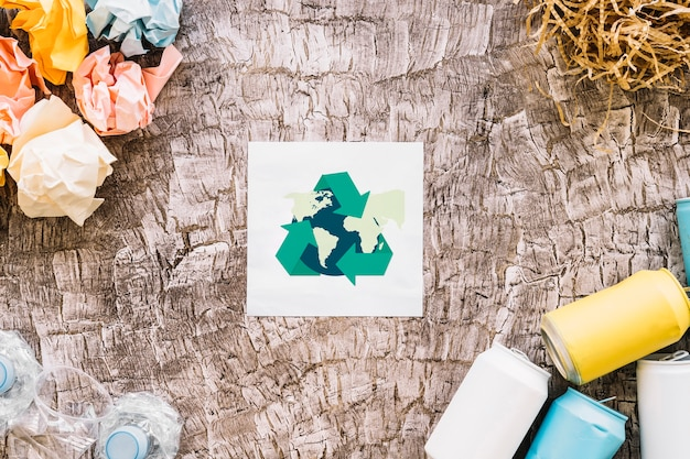 Globe with recycle icon surrounded by garbage Free Photo