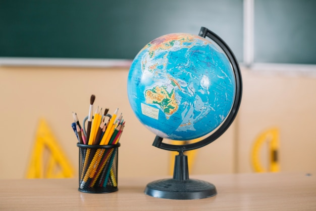 Globe and writing tools on school table Free Photo