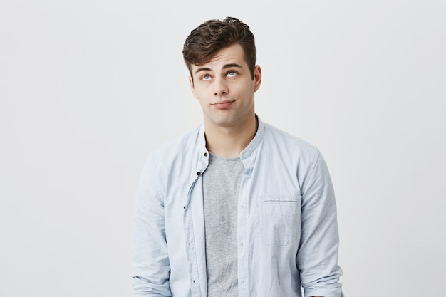Gloomy caucasian male student frowns face, looking upwards, pouting lips, being tired of his girlfriend`s stories. annoyed and tired young european man expresses annoyance and dissatisfaction. Free Photo