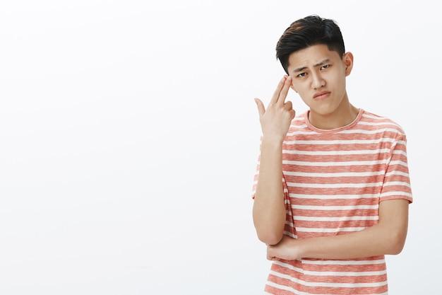 Ragazzo asiatico carino e cupo che soffre di noia che si sente incazzato e irritato mostrando il gesto della pistola vicino al tempio che ascolta il sopracciglio e fa smorfie dal dolore e dalla sensazione noiosa Foto Gratuite