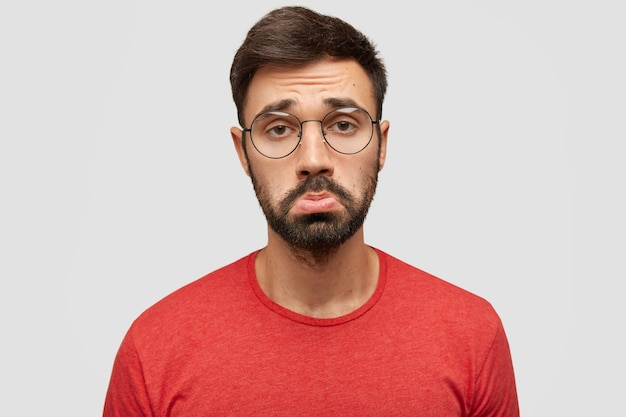 Gloomy displeased sorrowful bearded young male purses lips in discontent, being offended by bad comments of followers, expresses negativity, wears red jacket, stands against white wall Free Photo