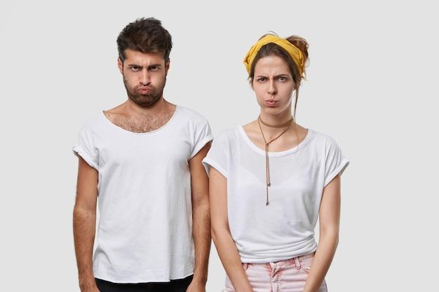 憂鬱な不機嫌そうな女性と男性が頬を吹く、喧嘩の後でお互いに話さない、意見の相違がある、悪い言葉に侮辱される、屋内で肩を並べて立つ、モックアップの白いカジュアルなtシャツを着る 無料写真