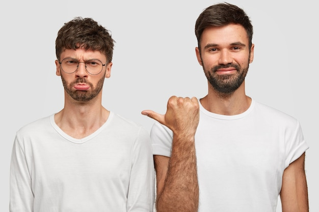 Gloomy unshaven young man model with grumpy expression, being in low spirit, stands near best man companion, wear casual white t shirts, express different emotions Free Photo