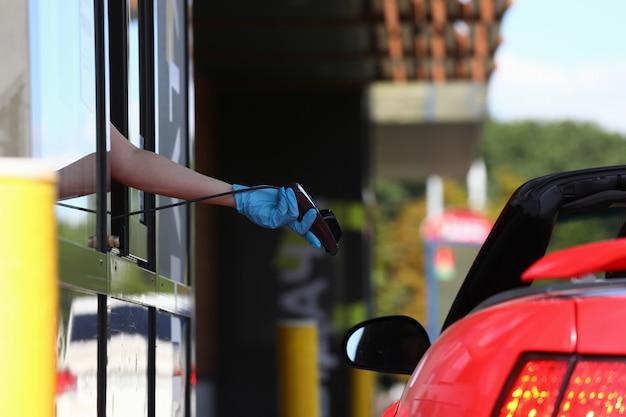 Рука в перчатке держит терминал pos и протягивает его к машине Premium Фотографии