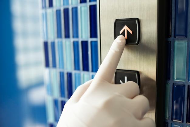 코로나 바이러스 오염을 방지하기 위해 엘리베이터 버튼을 누르는 장갑을 낀 손 무료 사진