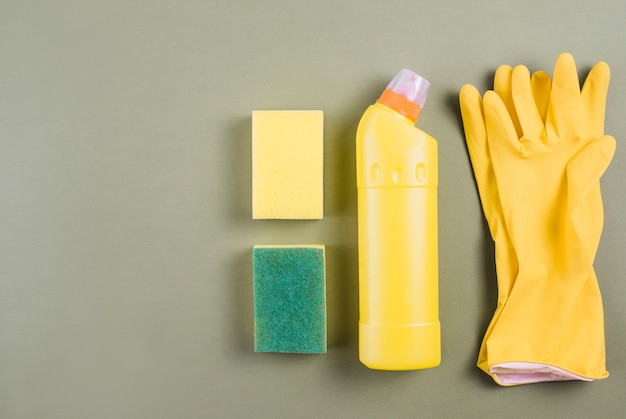 Gloves, detergent bottle and sponge on colored background Free Photo
