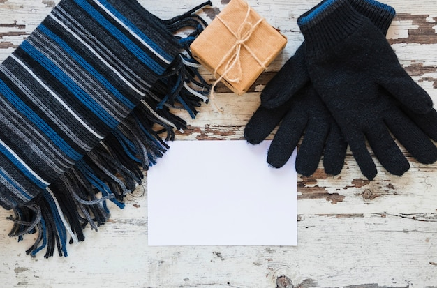 Gloves and scarf near gift and paper sheet Free Photo