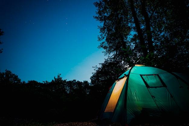 Светящийся голубой шатер в лесу под звездным вечерним небом. закат в лесу. летний пейзаж. Premium Фотографии