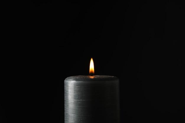 Светящаяся свеча на черном Premium Фотографии