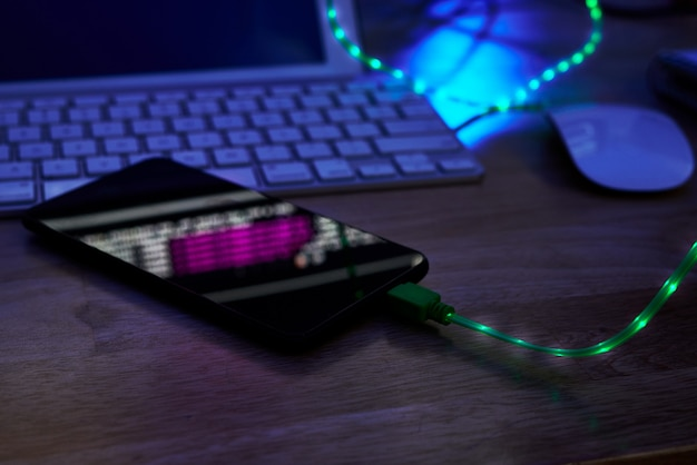 Glowing charging cable in smartphone lying on office table in darkness Free Photo