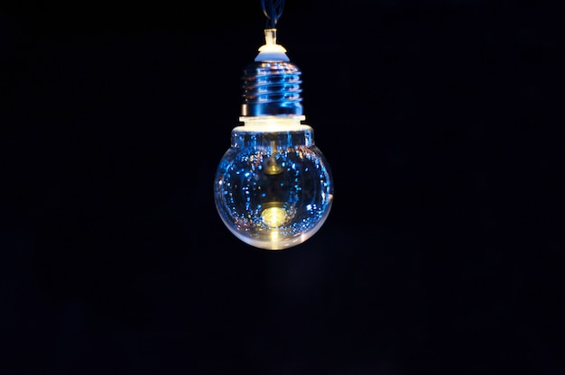 Glowing decorative light bulb on a dark background Premium Photo