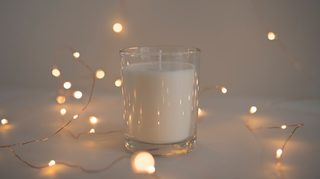 Glowing fairy lights around candle in candleholder Free Photo