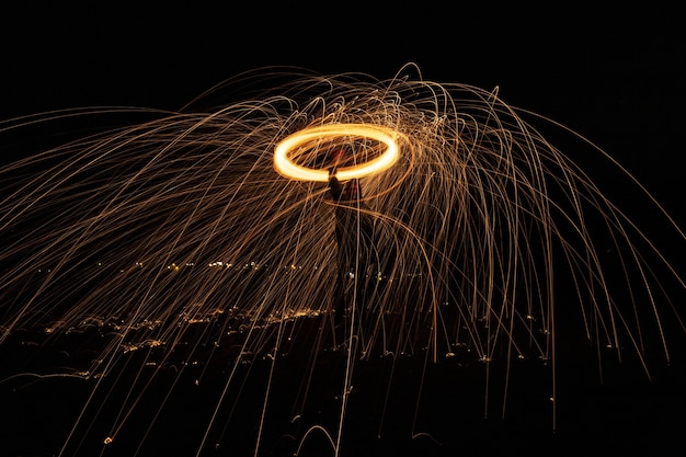 Glowing light extending its sparks into the air as it is rapidly spinning Free Photo