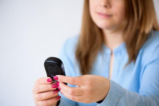 自宅のglucometerで血糖値をチェックする女性のクローズアップ Premium写真