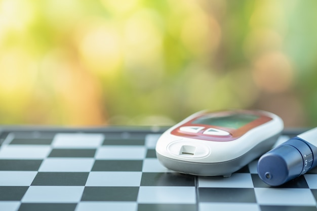 Glucose meter and lancet for check blood sugar level on chessboard. Premium Photo