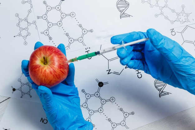 Gmo scientist injecting green liquid from syringe into apple - genetically modified food concept. Premium Photo