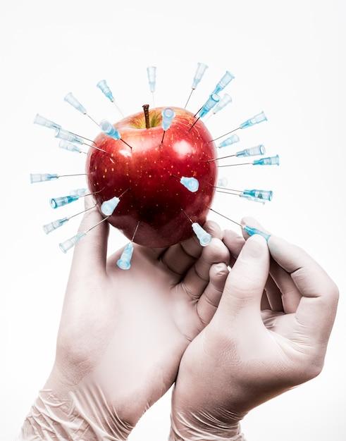 Gmoアップル。手にリンゴに化学物質を注入します。 Premium写真