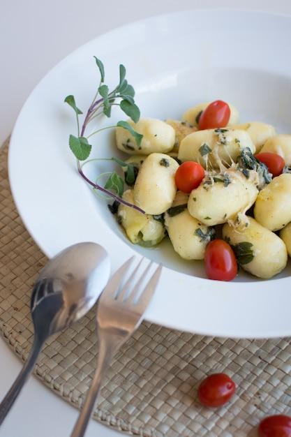 Gnocchi with cherry tomato and prosciutto Free Photo